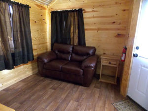 Spacious living area includes sofa, end table, dinette, and flat screen TV.